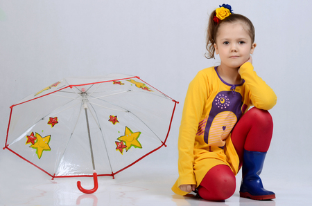 isolated on green: The little beautiful girl with an umbrella Stock Photo