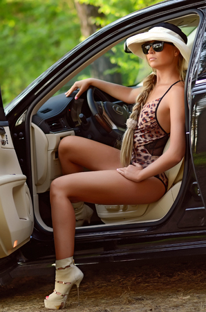 long sexy legs: sexy beautiful woman with blond hair posing in black luxury car Stock Photo