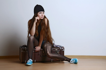 old women: Portrait of a beautiful young woman sitting on her old suitcase near the wall