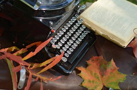 hojas antiguas: otoño Aún vida romántica con los libros, tela escocesa, maleta de la vendimia, vieja máquina de escribir y las hojas