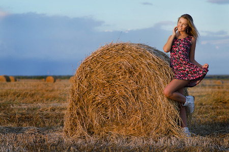 Photo of sexy blonde in a field with haystacks photo