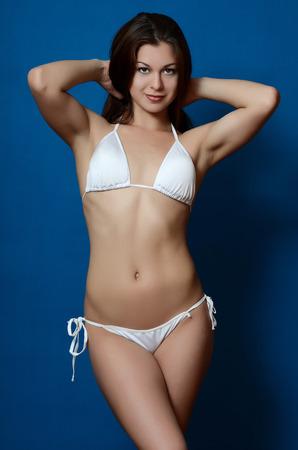 beaux seins: La jeune fille en bikini sur fond bleu