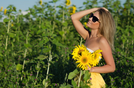 Portrait of a beautiful young blonde woman ion a background field of sunflowers photo