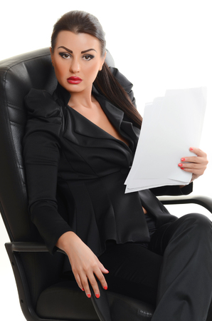 businesswoman suit: Portrait of a confident young woman sitting in an armchair  with documents