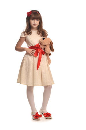 child model: Beautiful little girl in fashion dress holding lovely toy Stock Photo