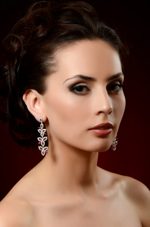 The beautiful woman in jewelry earrings close-up photo