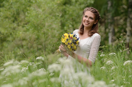 Beautiful natural young blonde smiling woman on field keep in hand yellow flowers photo