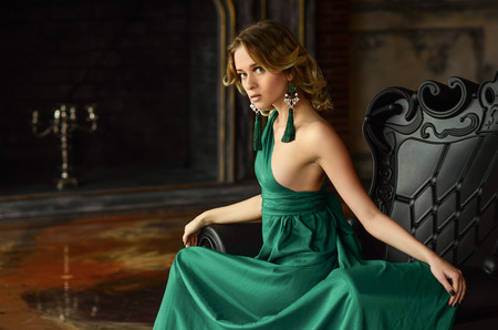 vintage woman: Elegant young woman in green evening dress posing in vintage interior. Fashion shot.