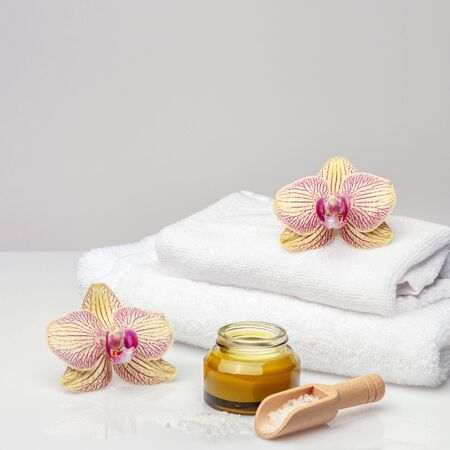 SPA composition. Towels, orchids, salt and cosmetic jar on a bright background. Reklamní fotografie
