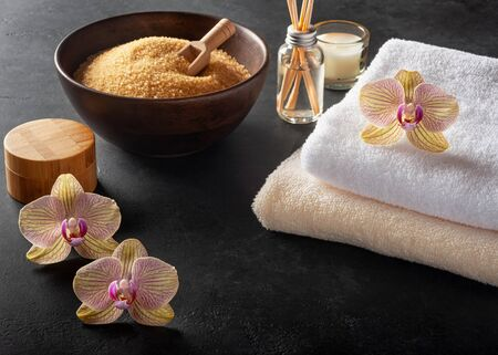 SPA background. Towels, orchids and cosmetics on a black background Reklamní fotografie
