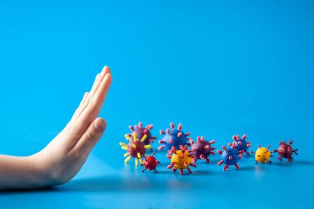 Stop epidemic concept. Child hand and artificial models of viruses on a blue background.