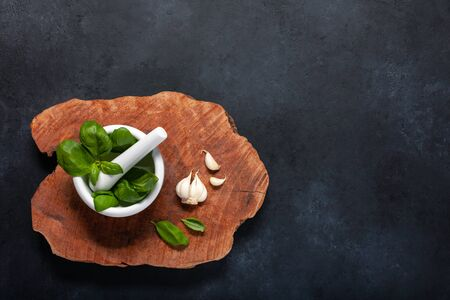 Basil leaves and garlic on a wooden board. Black background. Copy space. Top view.