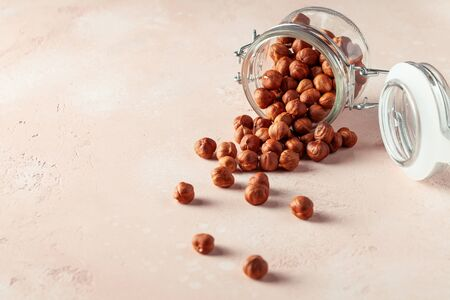 Hazelnuts in a glass jar on the table. Copy space.