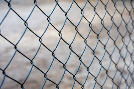 Stretched metal mesh on a blurred background . Fence from a metal grid