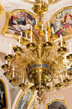 Large gilded chandelier in the temple of God on the background of icons and murals Stok Fotoğraf