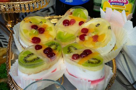 Jelly from milk, sour cream, kiwi and other fruits. Several large jellies lie on a plate