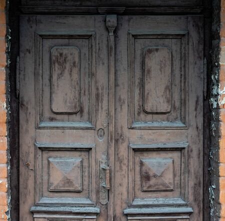 Old wooden doors are painted brown with colorless paint