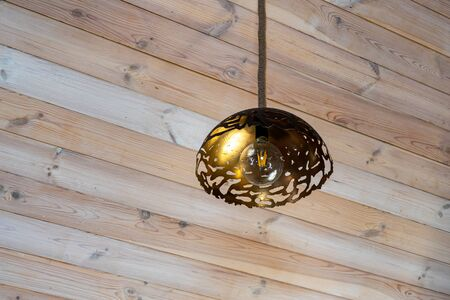 Energy saving lamp on a wooden ceiling. The interior design