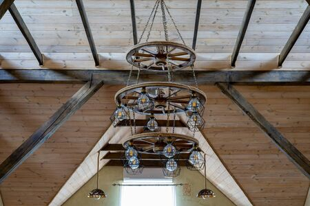 A large chandelier hangs from the ceiling of a wooden house. Wooden interior