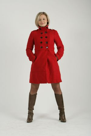The beautiful young girl-blonde dressed in a brown dress and a red coat.  photo