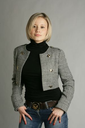 The beautiful young girl-blonde in a black polo-neck, a jacket and dark blue jeans photo