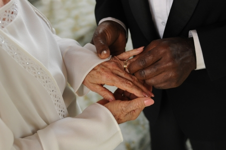 wedding vows: Mature mixed  couple exchaning vows and wedding rings a wedding ceremony