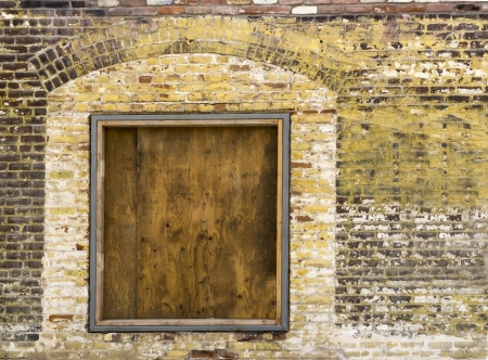 A old exterior brick wall with an old boarded up window ready for your content Imagens