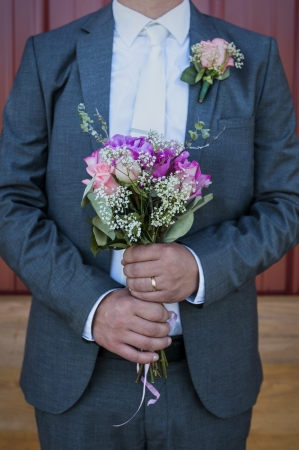 Groom holding Brides bouquet on the wedding day  Imagens