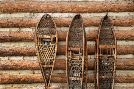 log cabin in snow:   pair of vintage snow shoes hanging on a cabin Stock Photo
