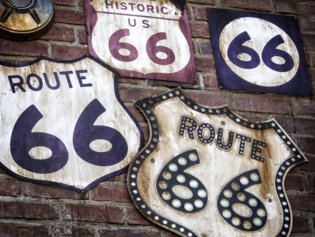 A Collection of vintage Route 66 signs displayed  on a old brick wall