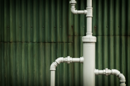 Gray pipes run down in front of a deep green corrugated grunge wall Imagens