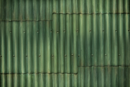 A green corrugated sheet metal wall with seams and bolts running the length of the image Imagens - 24551856