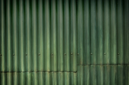 A green corrugated sheet metal wall with a seam and bolts running the length of the image Imagens - 24551859