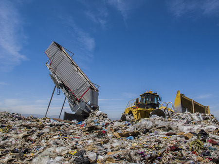 empties: Modern  hydraulic disposer empties a complete trailer, while bulldozer manages landfill.