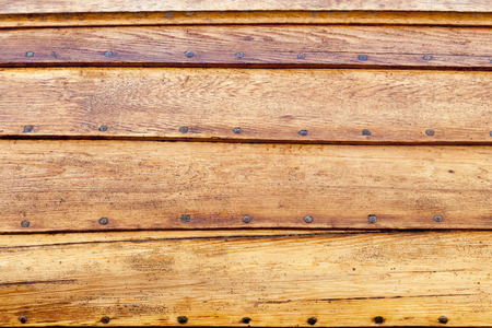 Side of a golden pine wooden boat thats shiplaped