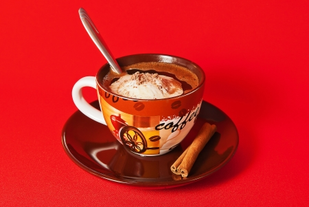 cup of coffee on a saucer with two sticks of cinnamon taken off on a red background photo