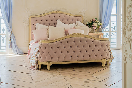 Vintage bed with the pillows in luxury clean bright white bedroom interior