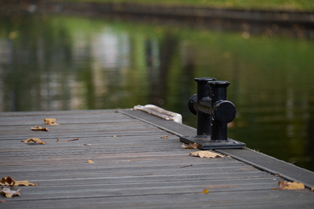 Black metal mooring bollard on a wooden pier at a lake with copy space, detail with selected focus and narrow depth of field Stock Photo