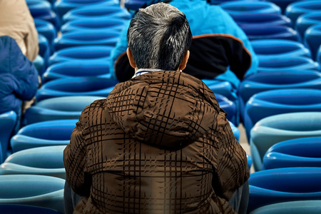 Lonely football soccer fan at empty stadium.