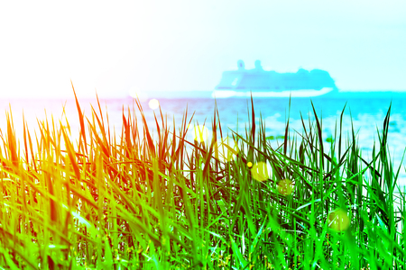 Green grass with a blurried unfocused cruise ship sailing away on sunset horizon. Vacation conception. RGB toned with a colorful lens flare.
