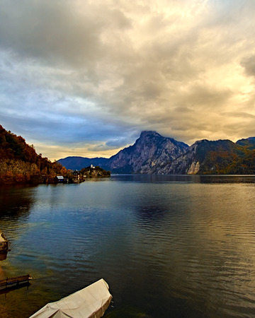 Beautiful scenic sunset over Austrian alps lake. Wooden boat house in alps in Hallstatt mountain village at the lake. Location: resort village Hallstatt, Salzkammergut, Austria, Alps. Cold toned.