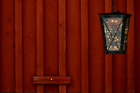 Old vintage lantern with vintage garland light inside at the rural red wooden wall. Christmas vacation decorations concept with a copy space for text. Stock Photo