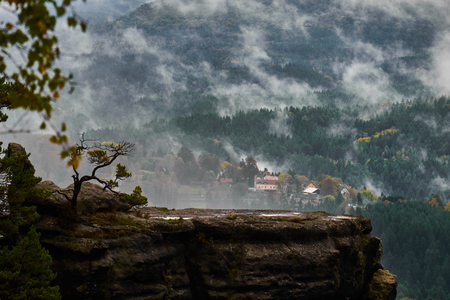 Misty rainy morning landscape with the sand rocky montains in Bohemian Saxon Switzerland in autumn colors. Imagens