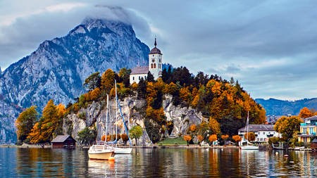 Panoramic scenic sunset over Austrian alps lake. Boats, yachts in the sunlight infront of church on the rock with clouds over Traunstein mountain at the alps lake near Hallstatt Salzkammergut Austria.