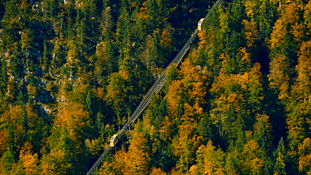 Beautiful aerial fall view of cable car ropeway funicular in austrian alps. Red cable railway car in the mountains by resort village Hallstatt, Salzkammergut, Austria, Alps.