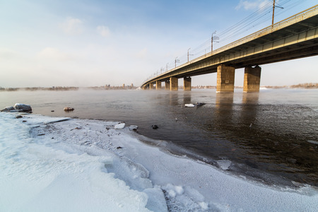 A metal bridge over the icy Enisey river in Krasnoyarske photo