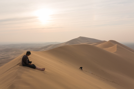 One person sits on top of the dunes of the desert, and the other climbs to the top