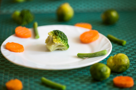 Vegetarian vegetables: broccoli, Brussels sprouts, carrots and green beans on a white plate and green background. Selective focus Stock Photo