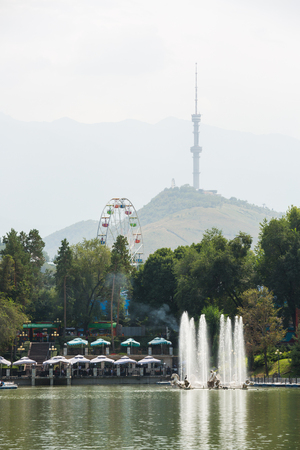 Pond in the amusement park in the afternoon. Almaty TV tower and mountains are in the background. Almaty, Kazakhstan. Stock Photo