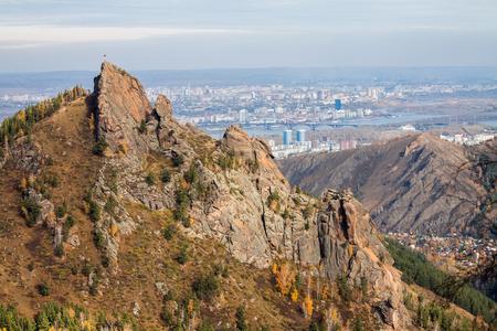 Mountain Takmak in the reserve Krasnoyarsk Pillars. West side of the rock complex Takmak. Top view of the city of Krasnoyarsk Фото со стока
